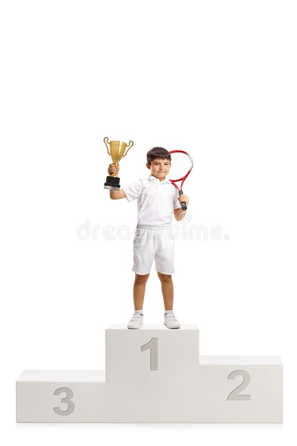 Boy first place tennis winner with a trophy cup standing on a winner`s pedestal stock photo