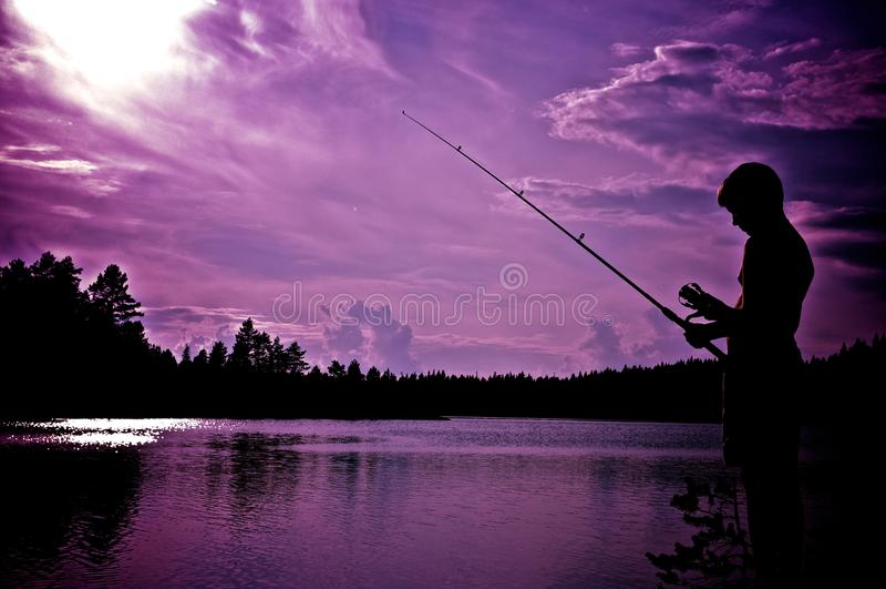 Boy fishing. A young boy fishing at a lake royalty free stock images