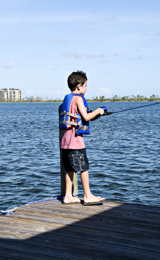Boy Fishing. Young boy fishing from the pier wearing a life vest royalty free stock images