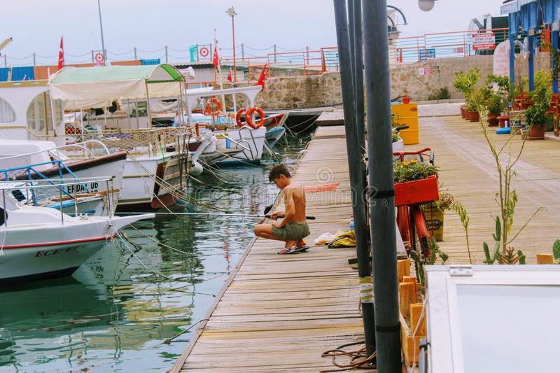 The boy is fishing on a fishing pole from the pier in the city harbor Antalya, Turkey in July, 2017 stock photo