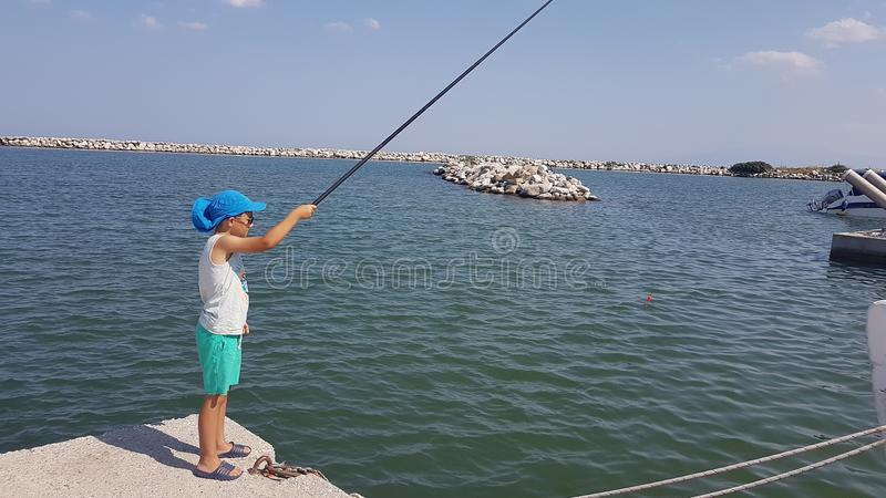 Boy fishing. In harbour royalty free stock image