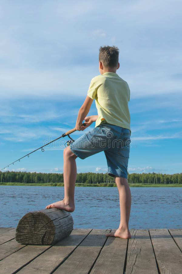 Boy fishing on the pier, against the blue sky and the lake, rear view royalty free stock photo
