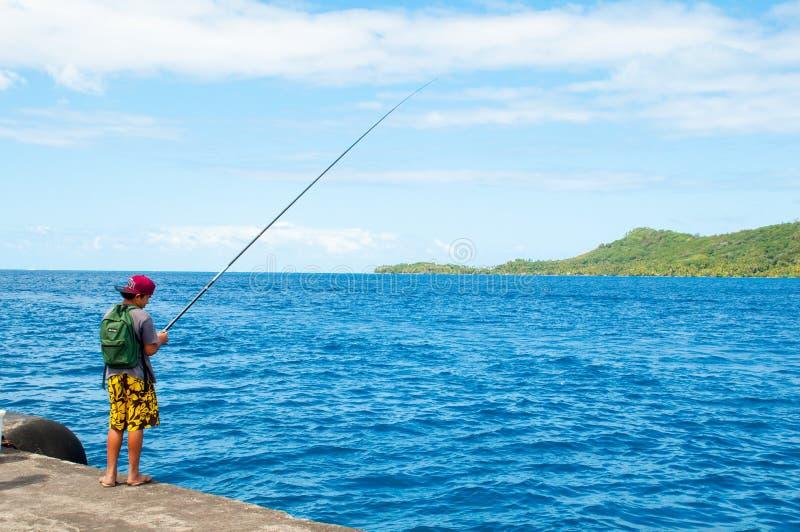 Boy fishing. On pier in French polynesia, Borabora, Pacific ocean stock photos