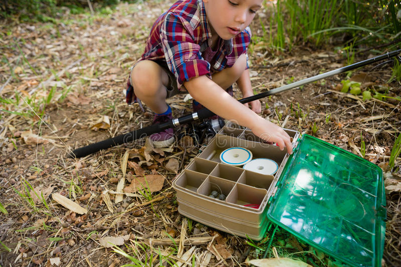 Boy with fishing rod searching in the box royalty free stock image