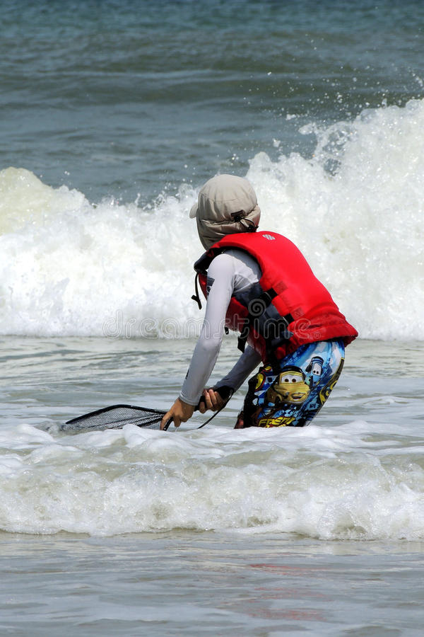 Boy fishing in the surf. A child wearing a red life vest and sun protective clothing is scooping his net through the surf. He is exploring nature, looking for stock photos