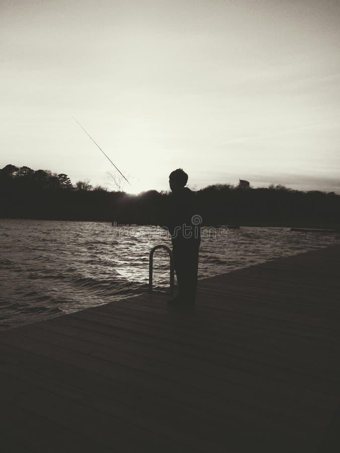 Boy fishing. At twilight royalty free stock photos