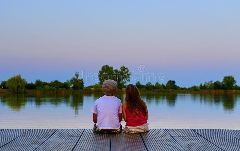 Boy with flat cap and little girl are sitting on pier. Boy and girl are looking on red sky. Love, friendship and stock photo