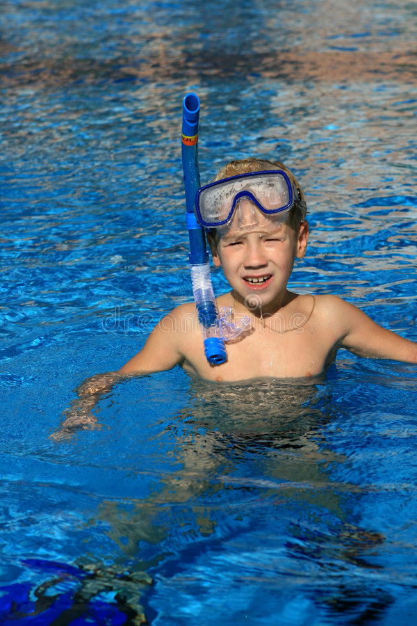 The boy floating in pool stock photography