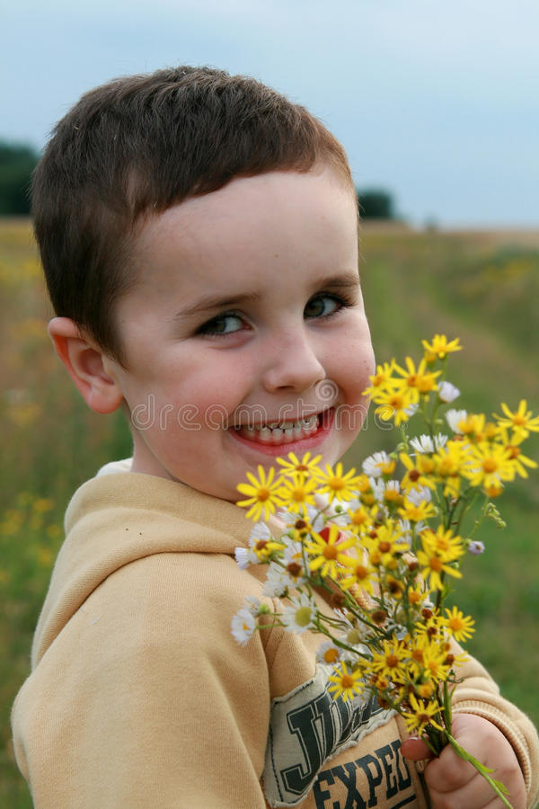 Boy with flowers for mummy. Boy with bouquet of flowers from meadow stock photo