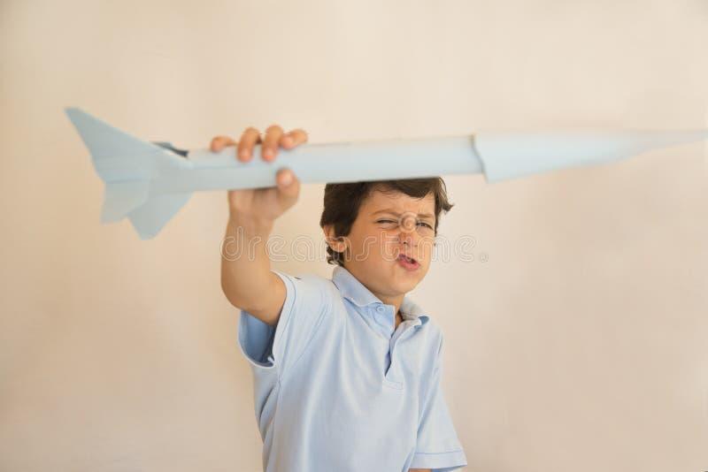 Boy flying paper rocket stock image