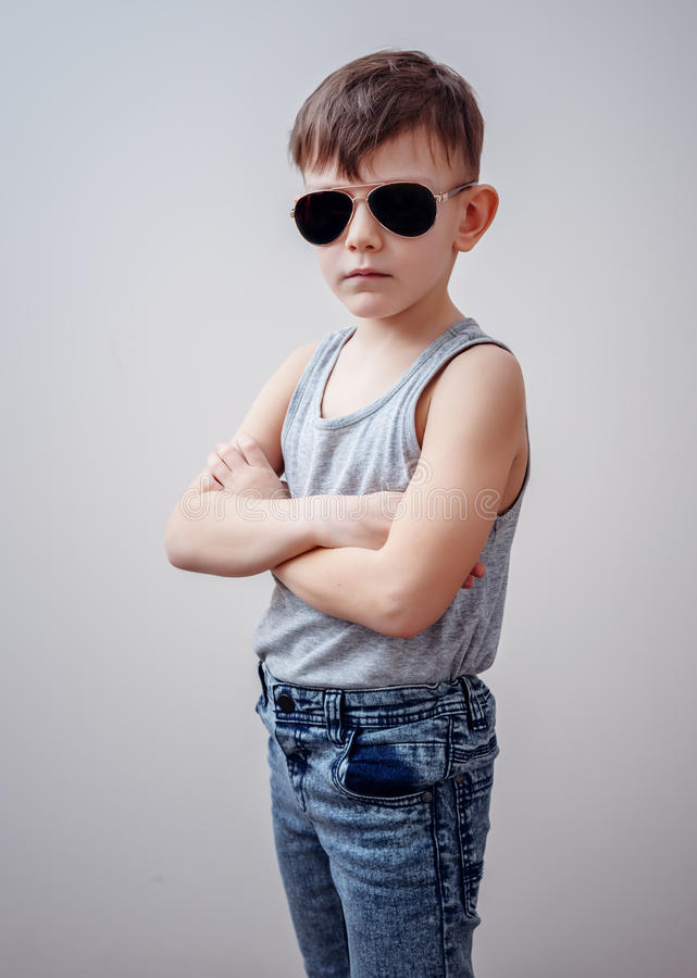 Boy with folded arms and sunglasses. Cute little single boy in sunglasses, sleeveless shirt and blue jeans with folded arms over gray background royalty free stock image