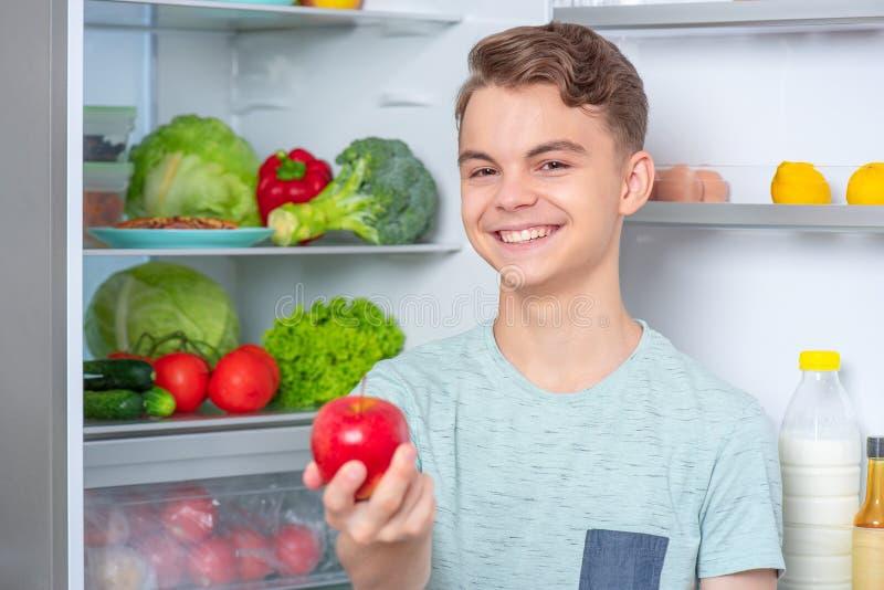 Boy with food near fridge stock image