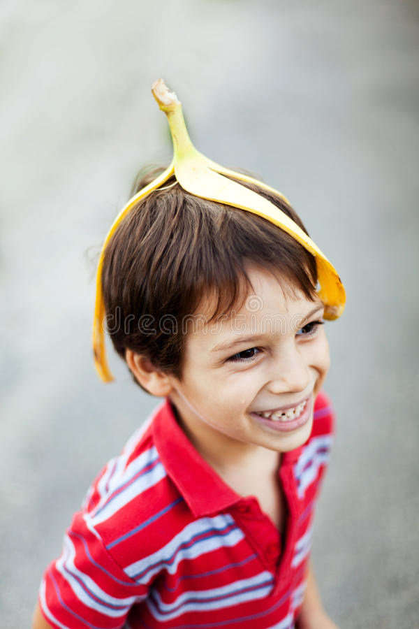 Boy fooling around. Wearing banana peel on his head royalty free stock image