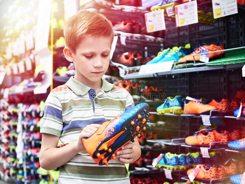 Boy with football boots in sport store royalty free stock photos
