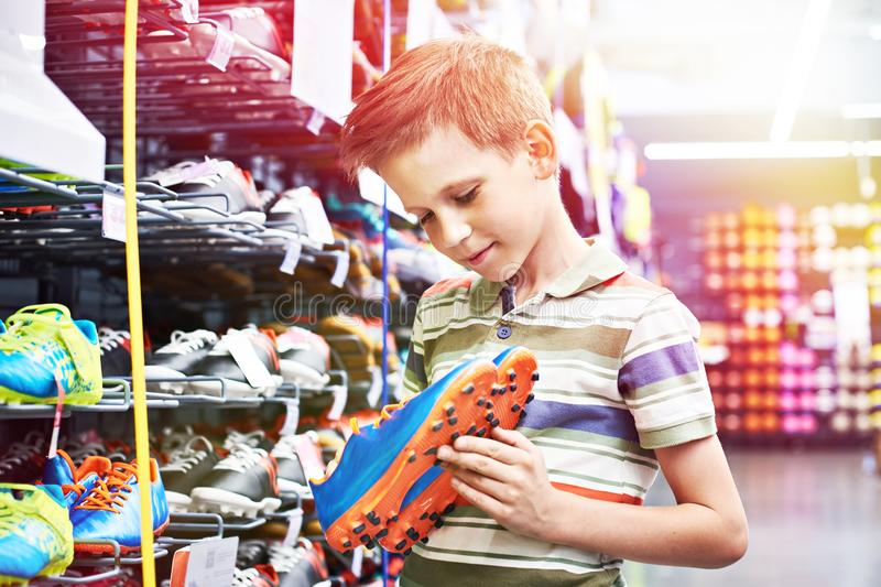 Boy with football boots in sport store stock images
