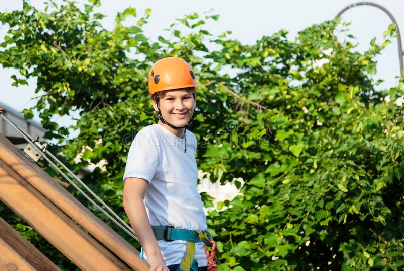 Boy in forest adventure park. Kid in orange helmet and white t shirt climbs on high rope trail. Climbing outdoor, amusement center stock photo