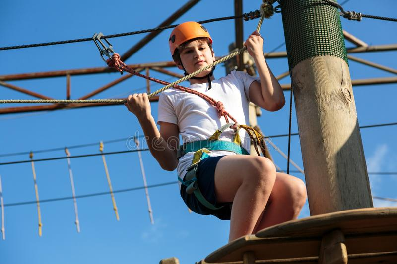 Boy in forest adventure park. Kid in orange helmet and white t shirt climbs on high rope trail. Climbing outdoor, amusement center royalty free stock photos