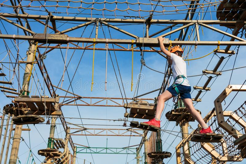 Boy in forest adventure park. Kid in orange helmet and white t shirt climbs on high rope trail. Climbing outdoor royalty free stock photo