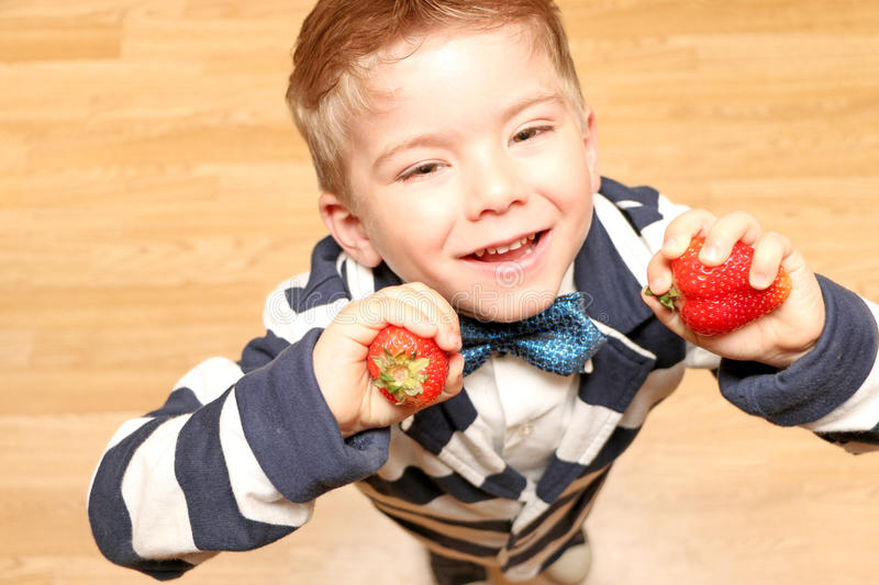 Boy four years holds strawberries. A little boy of four years old dressed in classical robes, looking up and holding a strawberry stock images