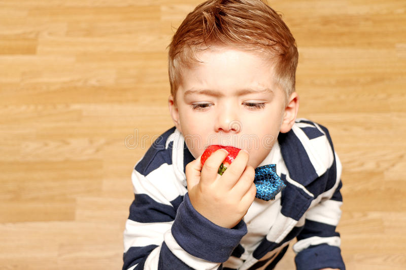 Boy four years, tries to eat strawberries. A little boy of four years wearing classic clothes and tries to eat the strawberries royalty free stock images