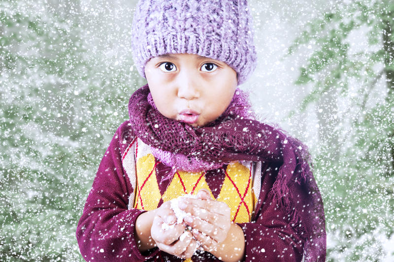 Boy is freezing in cold winter under tree. A boy is freezing in cold winter weather wearing beany and scarf stock photos