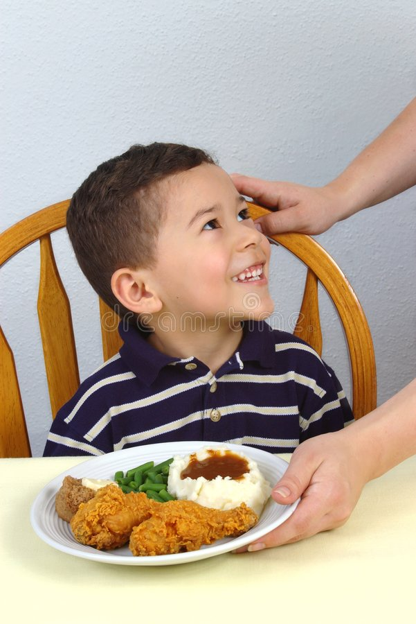 Boy and Fried Chicken Dinner. A young boy ready to eat his supper of fried chicken, mashed potatoes, green beans, and whole wheat roll royalty free stock photography