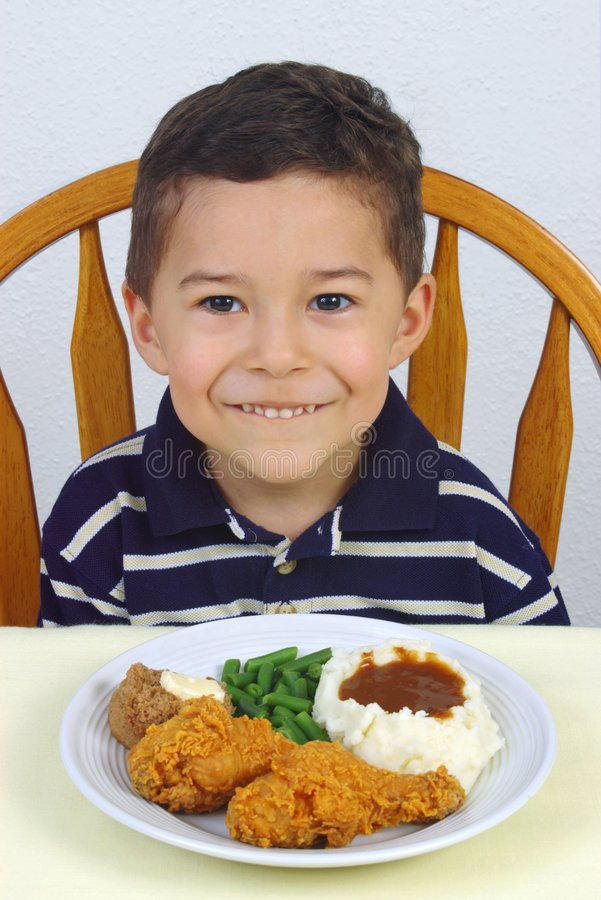 Boy and fried chicken dinner 5 years old. Boy ready to eat his dinner of fried chicken with mashed potatoes, green beans, and a whole wheat roll royalty free stock photos