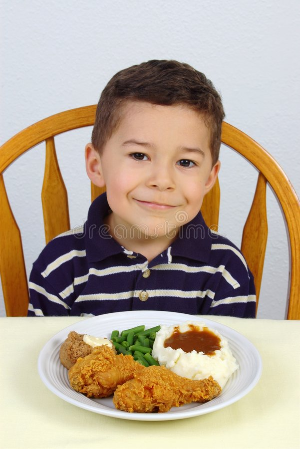 Boy and fried chicken dinner. Boy ready to eat his dinner of fried chicken with mashed potatoes, green beans, and a whole wheat roll royalty free stock photos