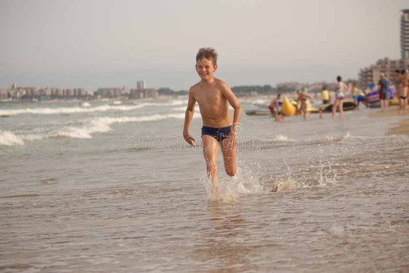 Boy frolics in the sea with splashes and waves royalty free stock photo