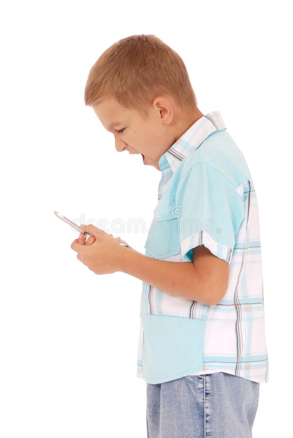 Boy is furiously screaming into his cell phone. A young boy is furiously screaming into his cell phone stock photography