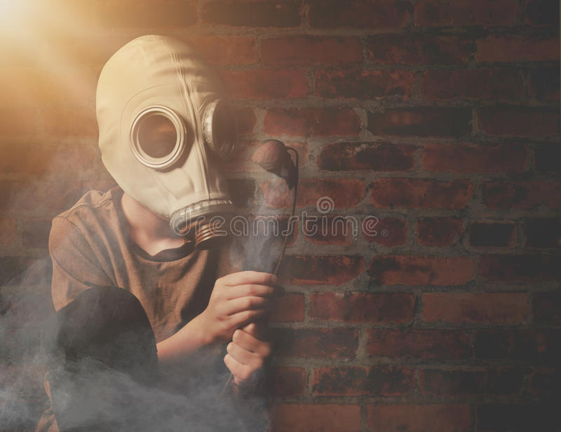 Boy in Gas Mask Holding Dead Flower with Smoke. A young boy is holding a dead flower against a brick wall with a gas mask and dangerous gas in the air for a stock photography
