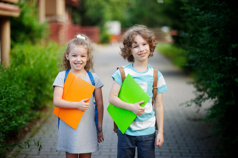 Boy and gerl on the way to school. Two pupils of elementary school. Behind the back of everyone a satchel, in hands - the bright folder. Children smile stock photos