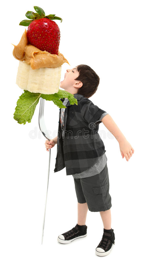 Boy Giant Fruit Fork Clipping Path. Young Boy with Giant Fork Eating Peanut Butter, Banana and Strawberry with Clipping Path royalty free stock photography