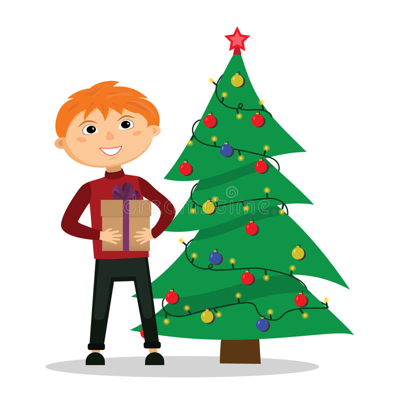 Boy with a gift in hands near the Christmas tree. stock images