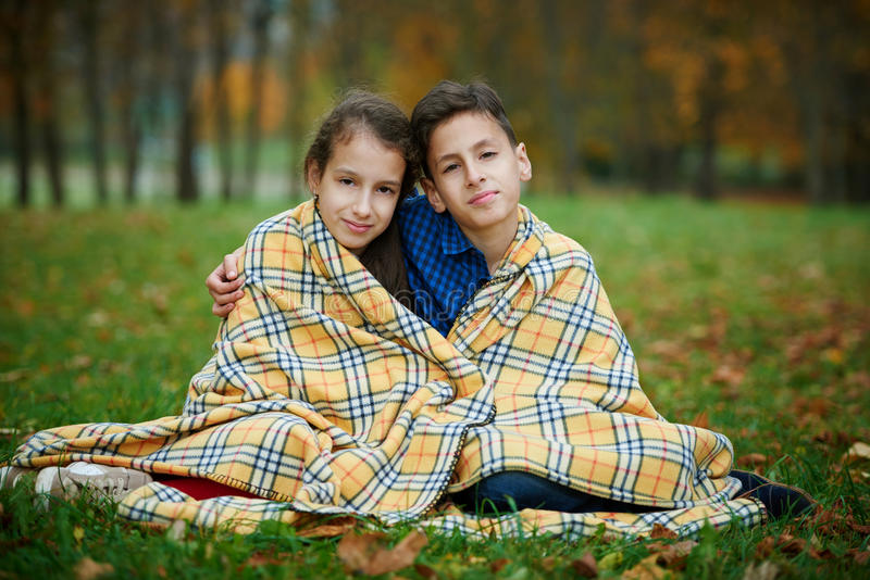 Boy and girl in autumn park stock photography