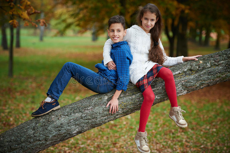 Boy and girl in autumn park stock photo