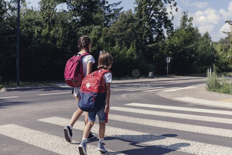 Boy and girl with backpacks walking on pedestrian crossing stock photo