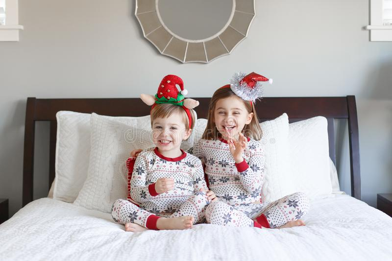 Boy and girl on bed with Christmas pajamas royalty free stock image