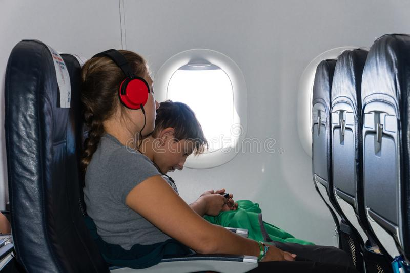 A boy and a girl listen to music sitting on the plane stock photo
