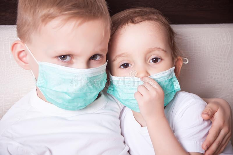 Boy and girl, a children in a medical mask. The concept of an epidemic, influenza, protection from disease, vaccination.  royalty free stock images