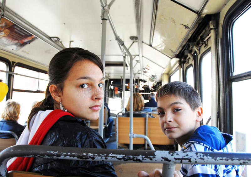 Boy and girl in city bus stock photo