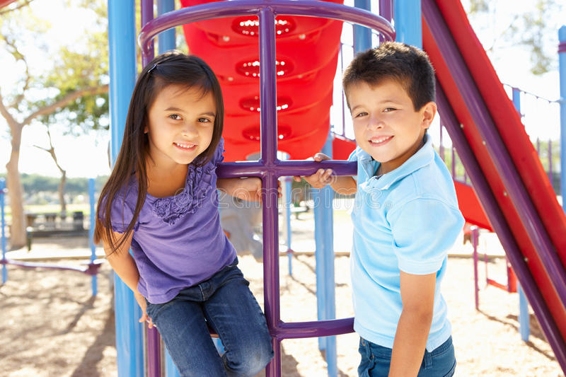 Boy And Girl On Climbing Frame In Park stock images