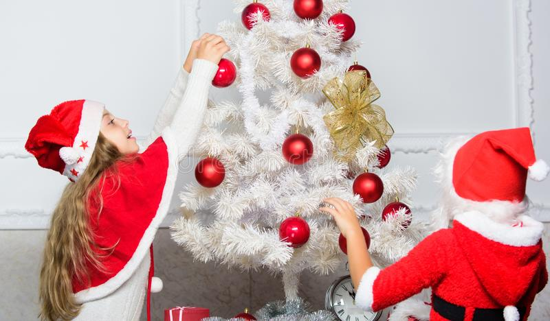 Boy and girl decorating tree. Cherished holiday activity. Kids in santa hats decorating christmas tree. Family tradition royalty free stock images