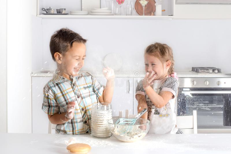 The boy and the girl do dough in kitchen. The play about with flour and cheerfully laugh stock photography