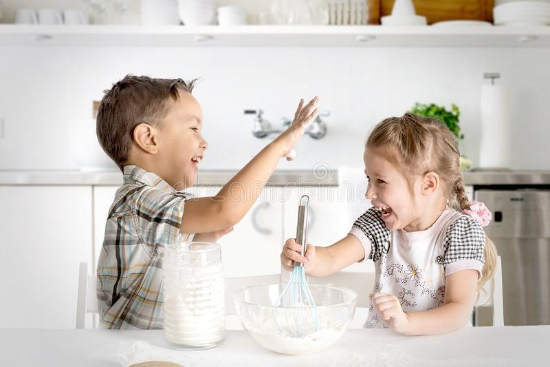 The boy and the girl do dough in kitchen. They play about. The littel boy and the girl do dough in kitchen. They play about with flour and cheerful laugh royalty free stock photography