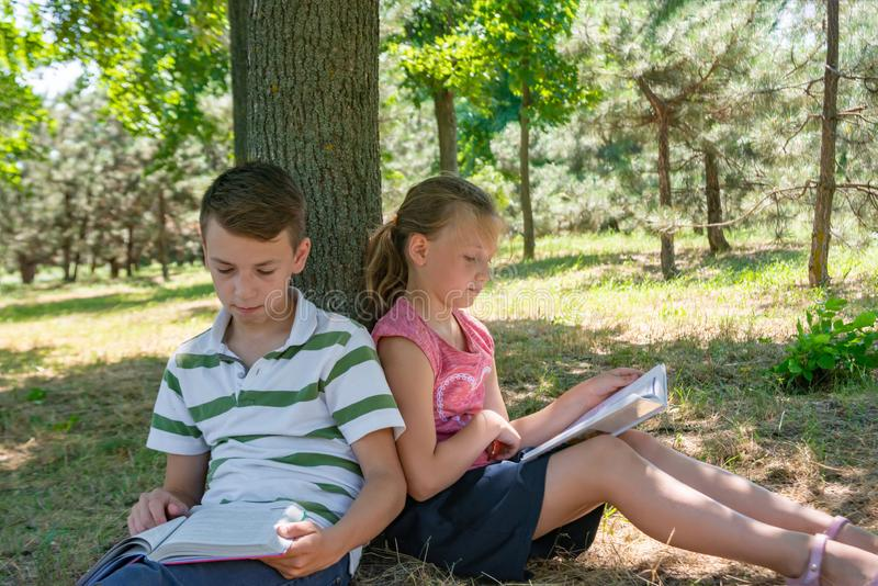 A boy and a girl do their homework in the park and get ready for school together.  royalty free stock image
