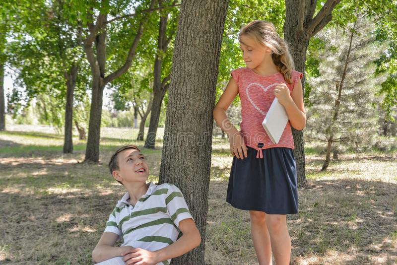 A boy and a girl do their homework in the park and get ready for school together.  royalty free stock photo