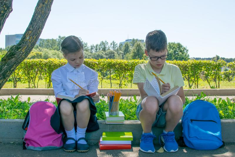 Boy with a girl doing school lessons, writing in a book royalty free stock photos