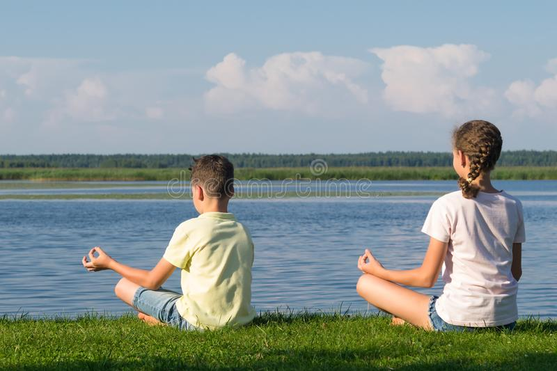 Boy and girl doing yoga outdoors by the lake stock photos