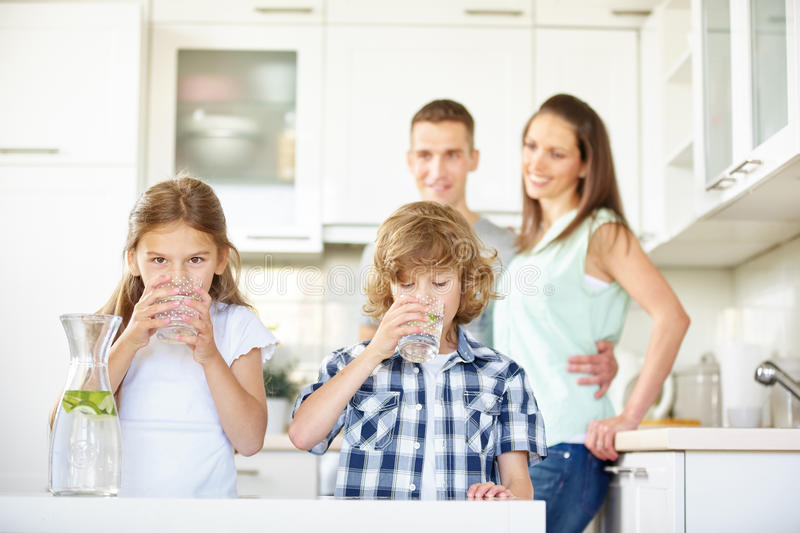 Boy and girl drinking water with lime. In the kitchen while the parents are watching stock photography